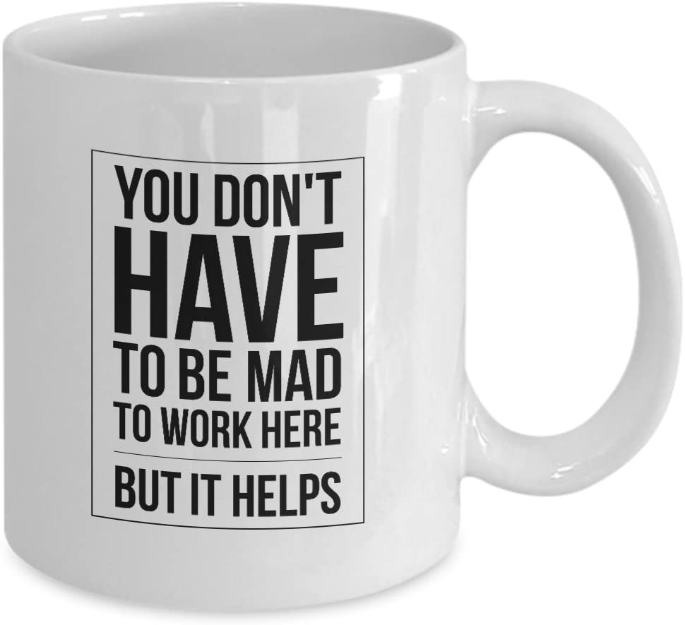 "A white mug with ""you don't have to be mad to work here, but it helps"" printed on it."